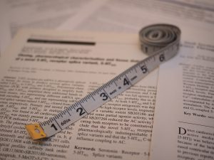 Et målebånd ligger oppå en (tilfeldig) vitenskapelig artikkel