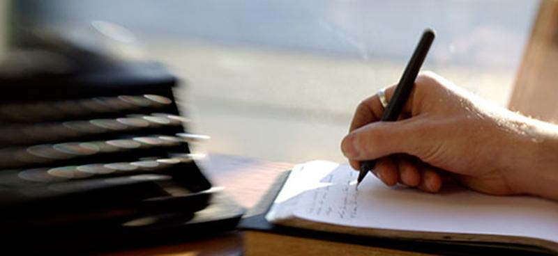 hånd som skriver innlegg med penn og papir